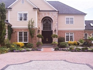 Grand front entrance brick driveway with cobble stone design inlay