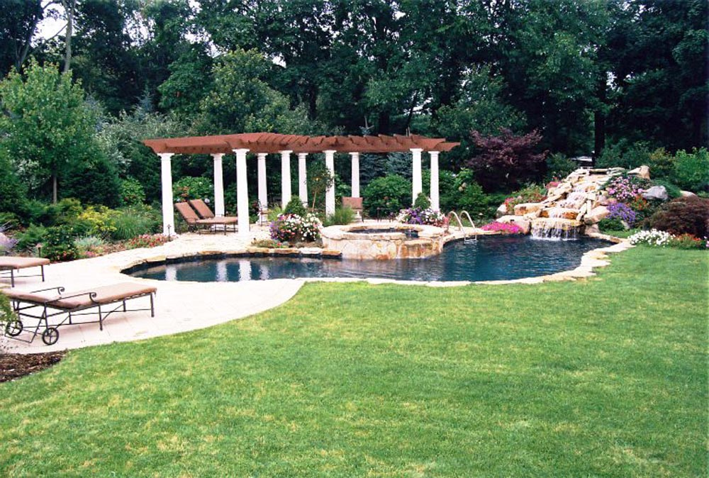 Pool with overflow hot tub and custom stone waterfall, pergola structure