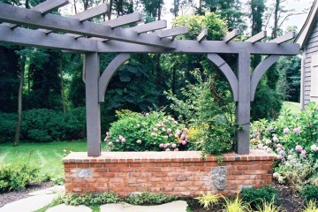 Brick wall foundation with granite accent timber frame pergola structure