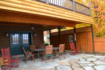 Rustic stone patio with log cabin accent overhead deck Schroon Lake